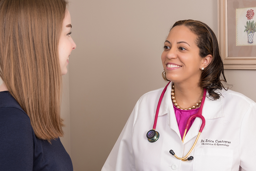Female doctor smiling at female patient