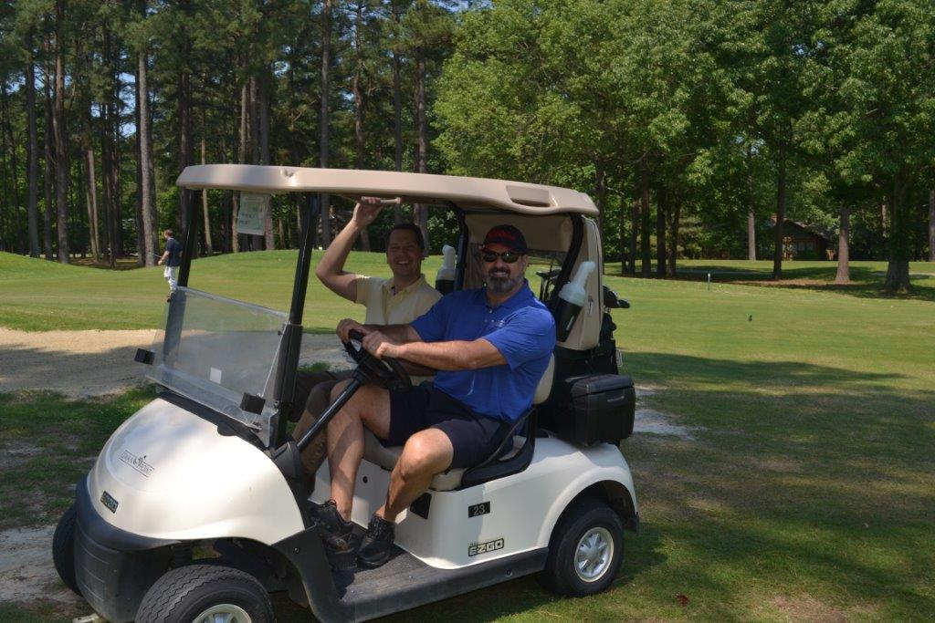 Golfers on golf cart at CRMC's 2019 Golf Classic event