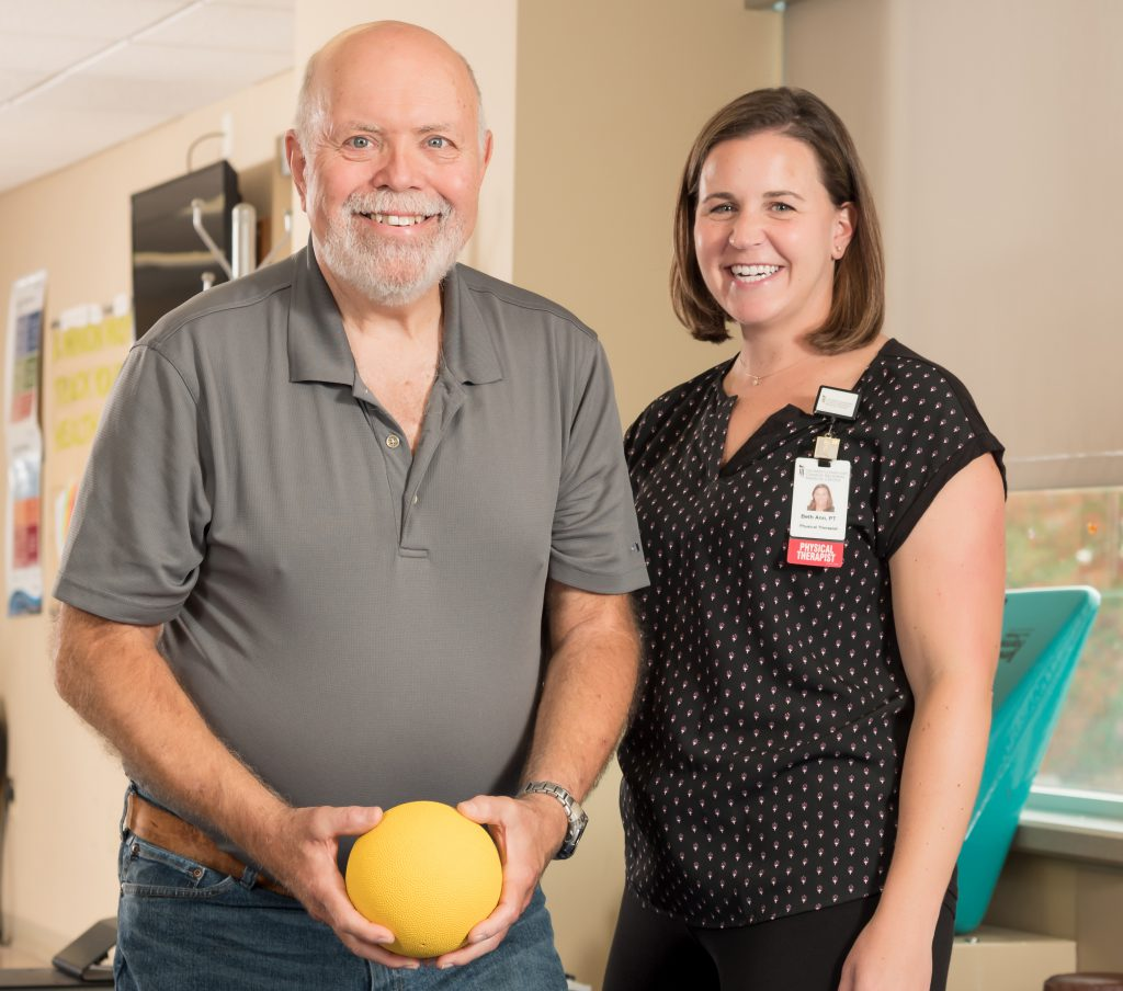 Colan Ratliff holding a medicine ball with Physical Therapist Beth Ann Galligan