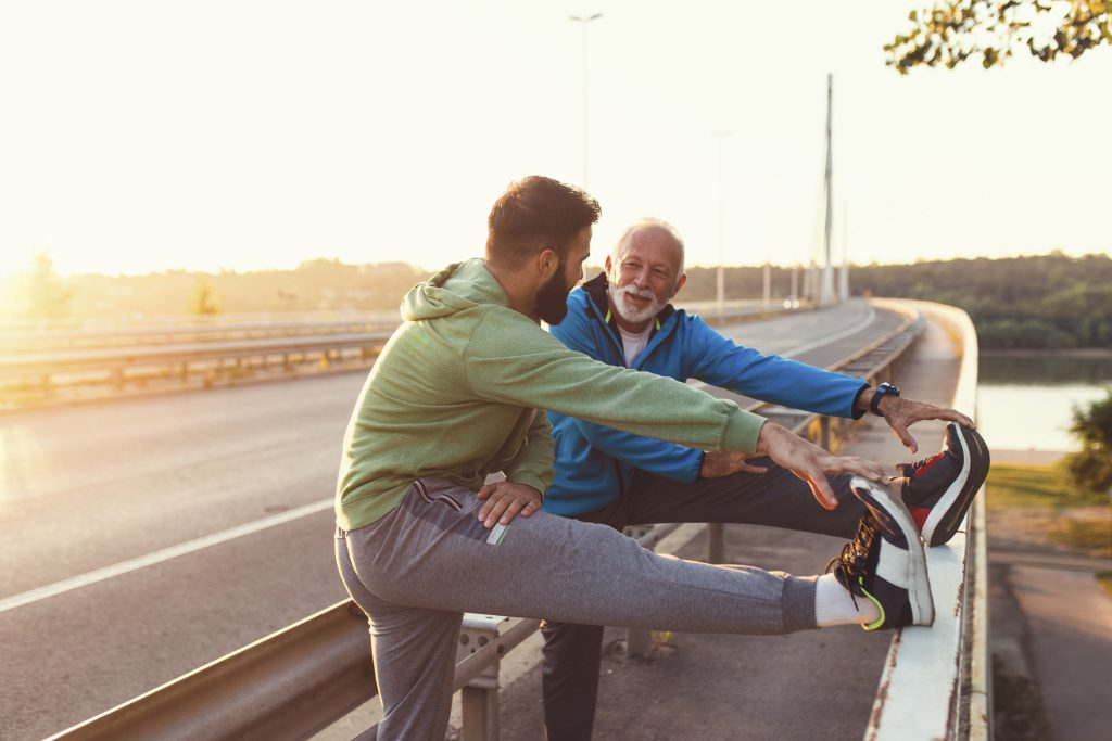 Happy father and son exercising together outdoors on big modern bridge