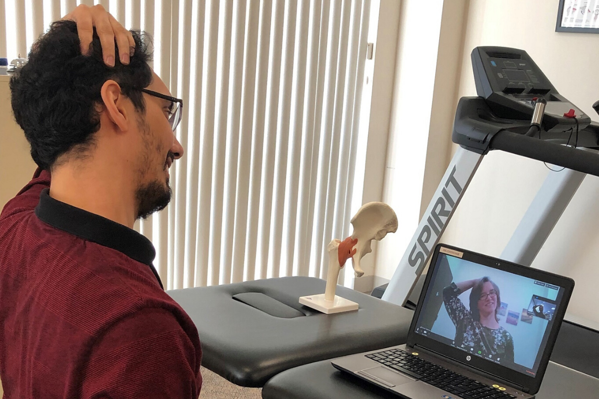 Physical therapist working with patient over video call on laptop
